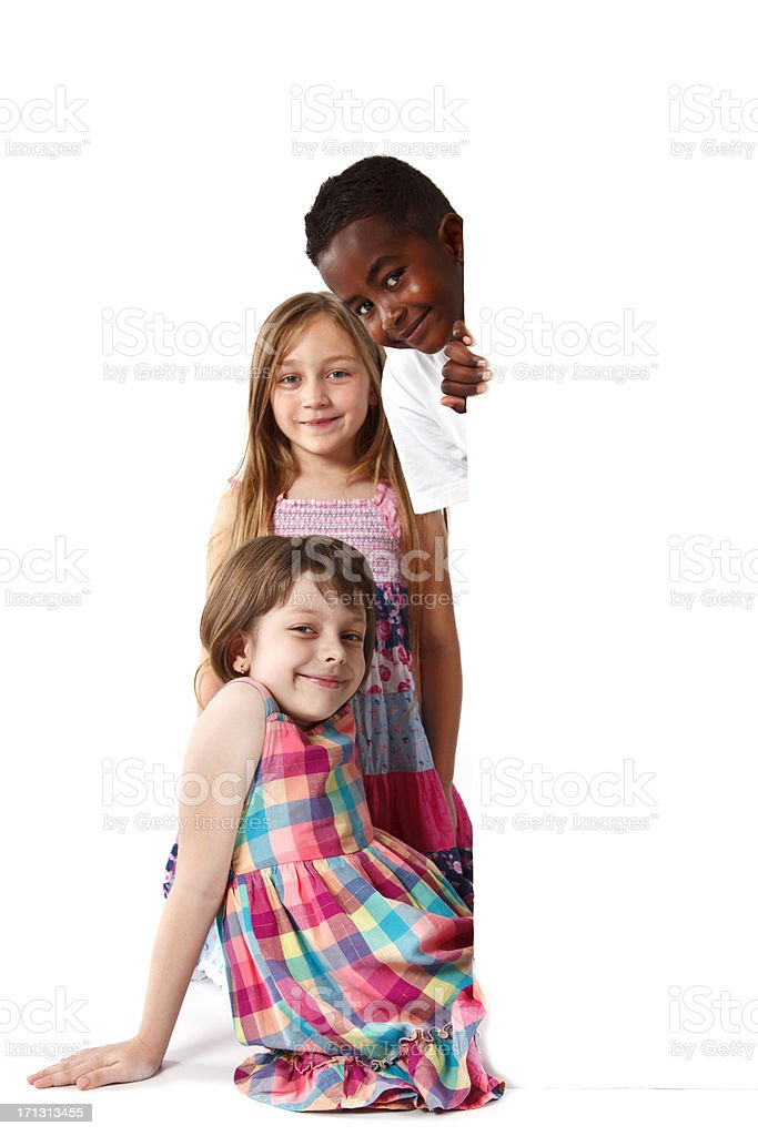 Group of multi-ethnic children peering round a white board royalty-free stock photo