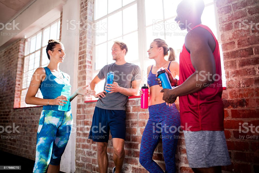 Group of multi-ethnic friends recovering and hydrating at the gym stock photo