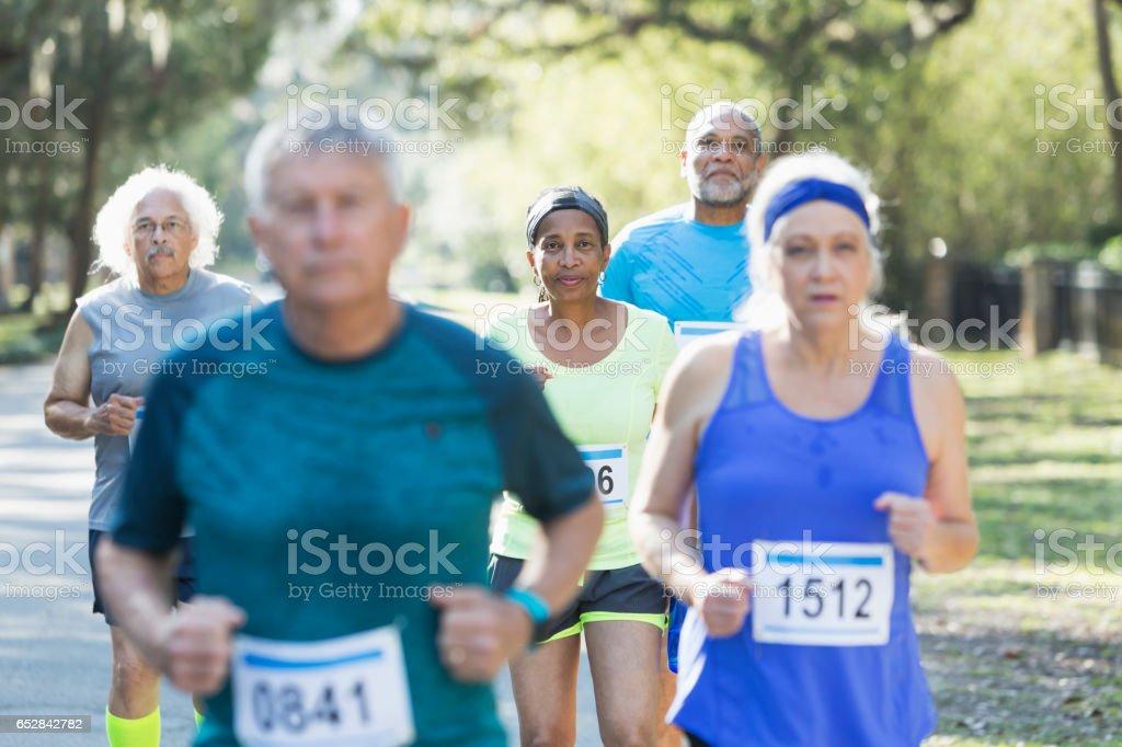 Group of multi-ethnic seniors running a race stock photo
