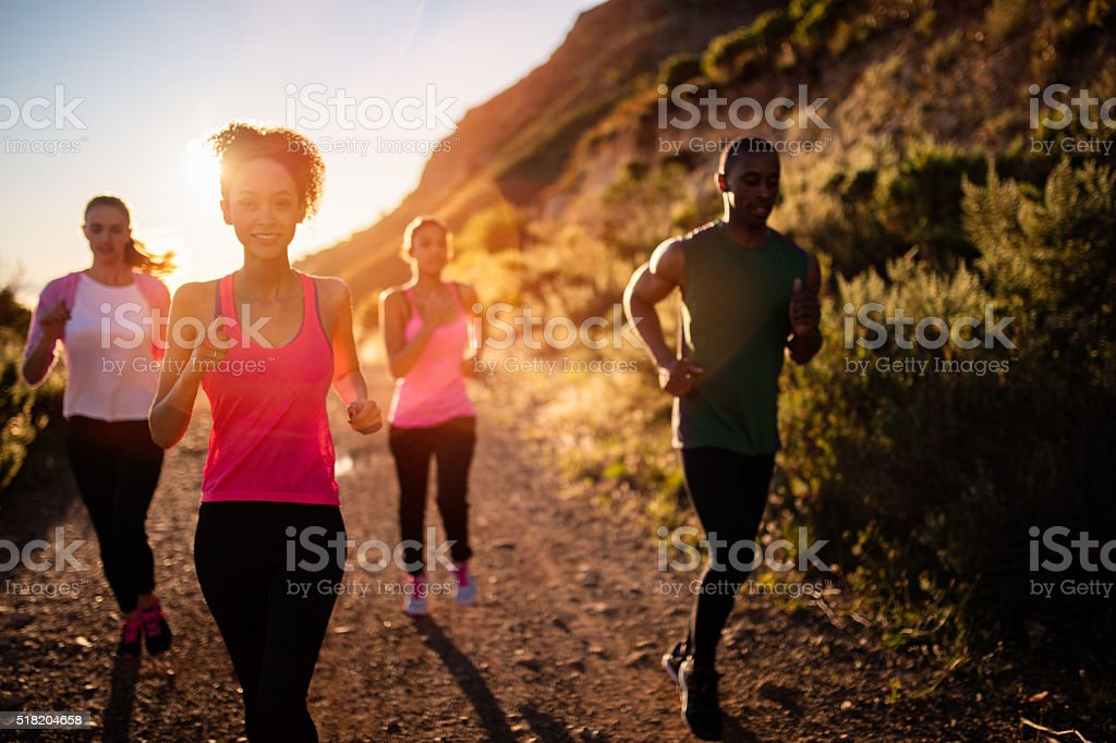 Group of multi-ethnical friends running outdoors stock photo