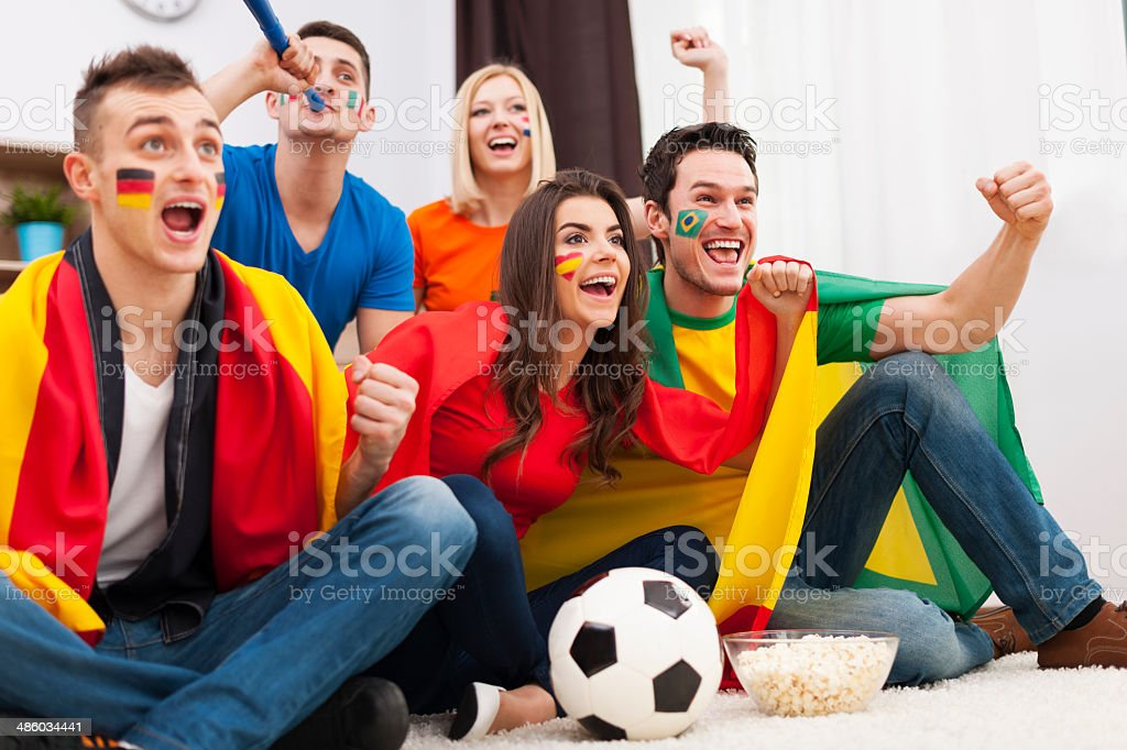 Group of multinational people cheering football match at home royalty-free stock photo