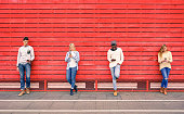 Group of multiracial fashion friends using smartphone outdoors