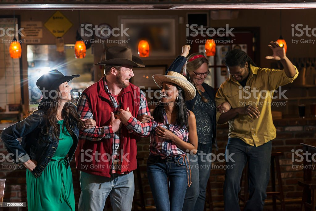 Group of multiracial friends dancing in cowboy hats stock photo