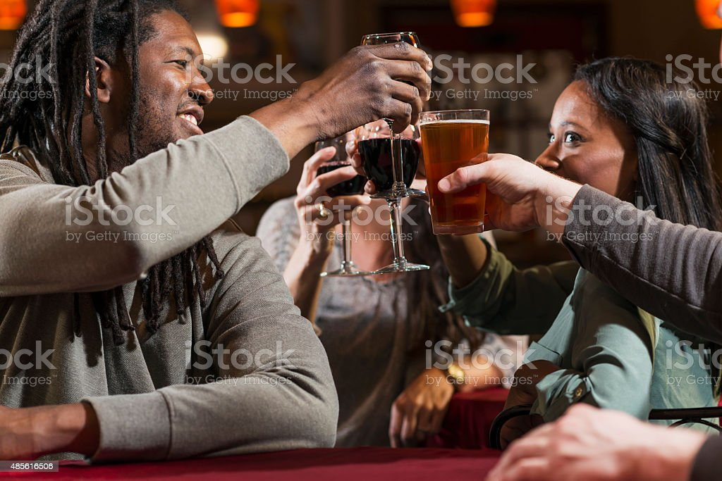 Group of multiracial friends drinking and toasting stock photo
