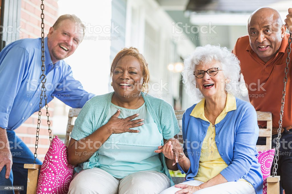 Group of multiracial seniors on porch swing stock photo