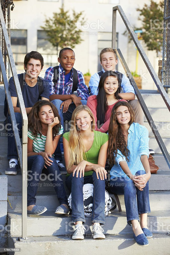 Group of multiracial teenagers sitting on the steps stock photo