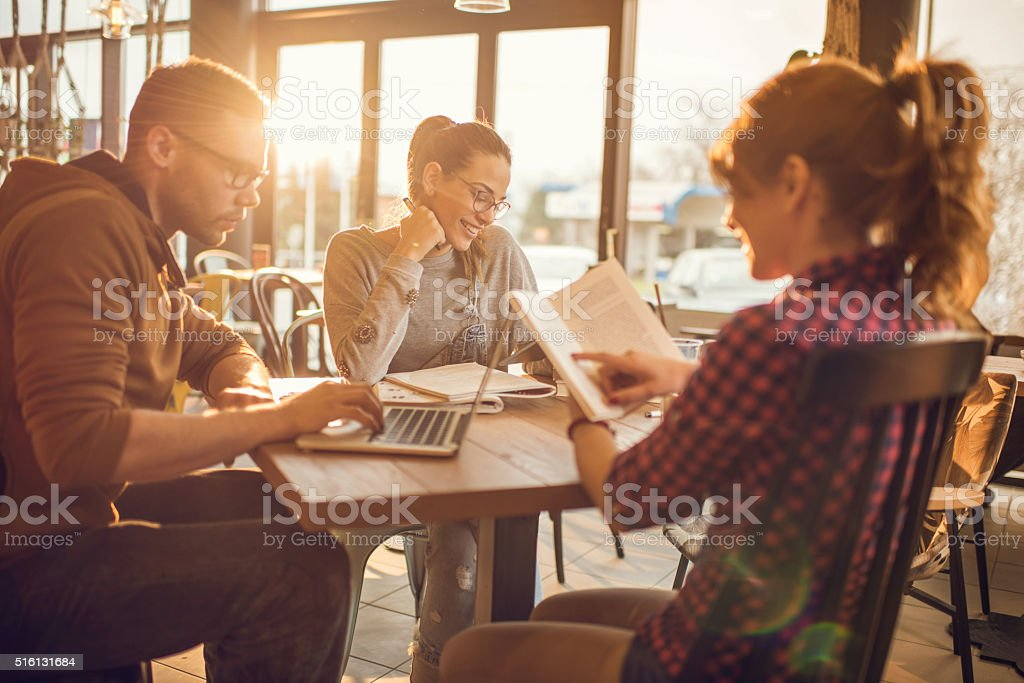 Group of multi-tasking college students in a cafe. stock photo