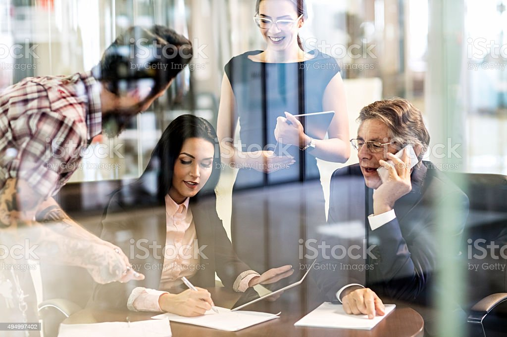 Group of multi-tasking creative people working in the office stock photo