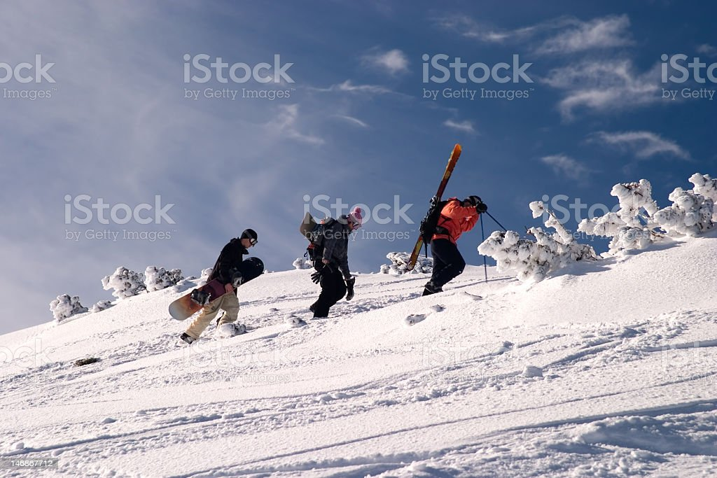Group of off-piste riders climing a slope royalty-free stock photo