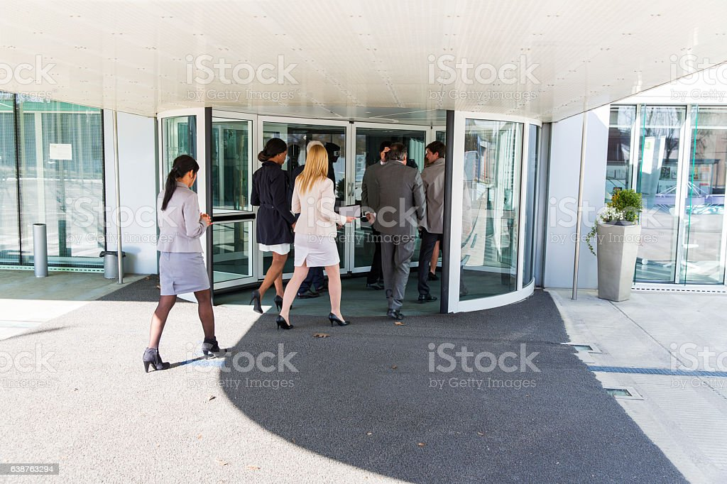 Group of ofiice worker entering in  revolving door stock photo