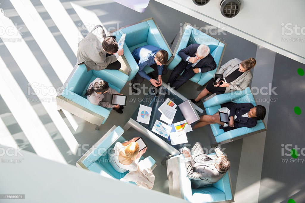 Group of ofiice worker sitting in lobby,discussing stock photo
