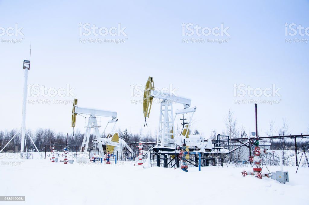 Group of oil pumps and wellheads stock photo