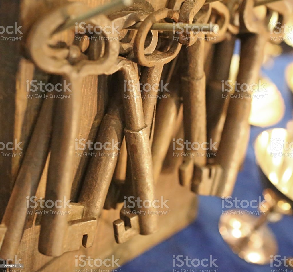 Group of old  and rusty keys hanged on wall stock photo