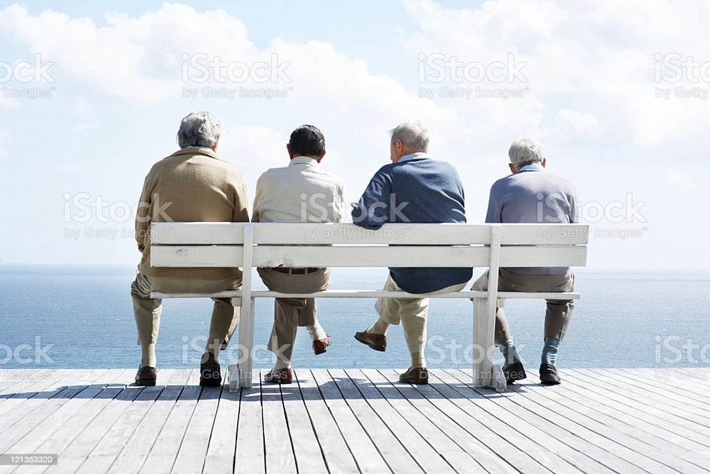 Group of old male friends sitting together on bench stock photo