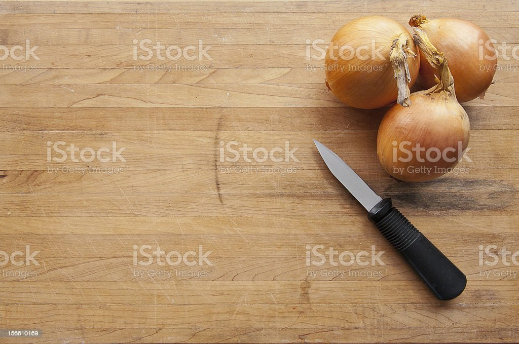 Group of onions with a knife on worn cutting board royalty-free stock photo