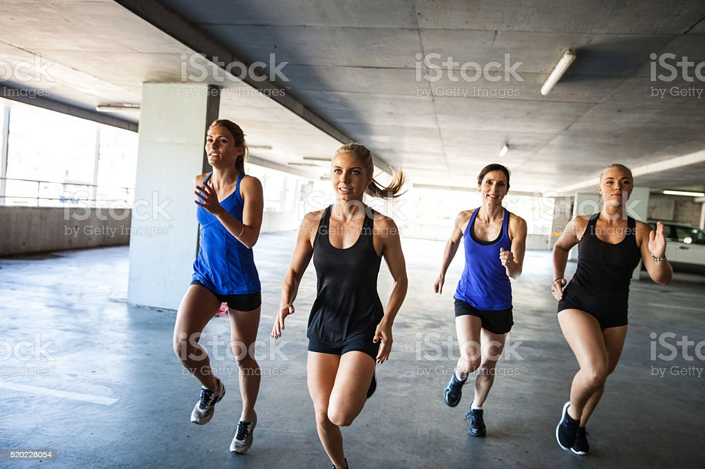 Group of only women running inside a parking stock photo