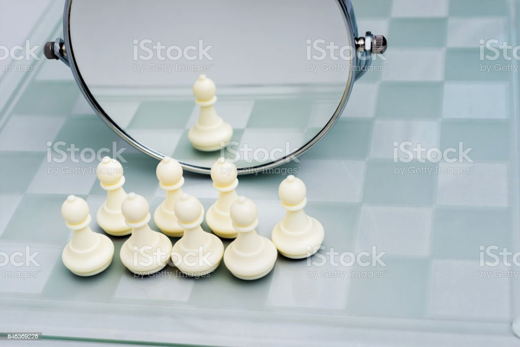 A group of pawns are in front of the mirror stock photo