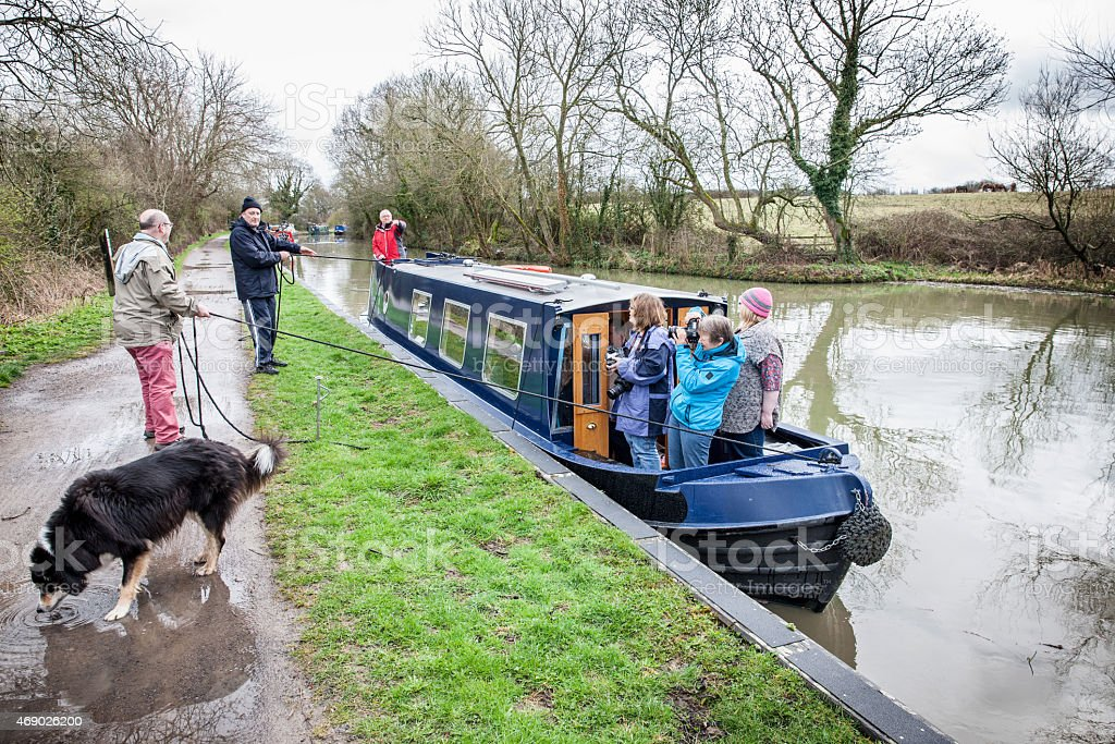 Group of people aboard canal barge mooring up stock photo