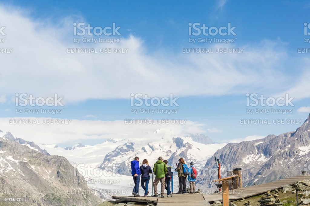 A group of people admire the Jungfrau-Aletsch glacier in front of them. stock photo