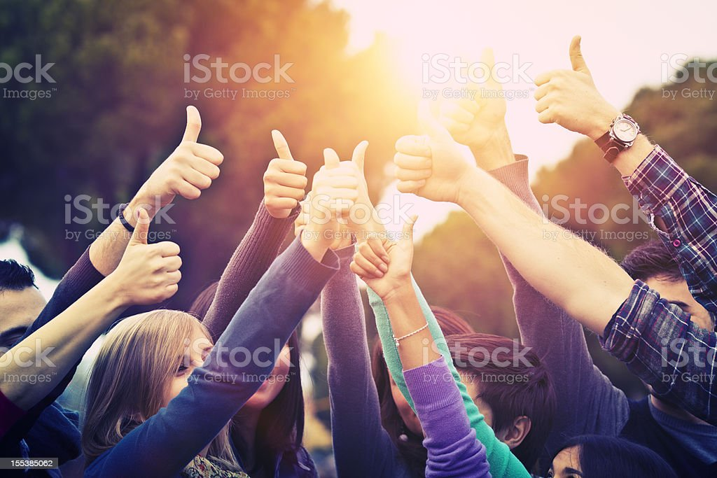 Group of people all raising arms with thumbs up stock photo