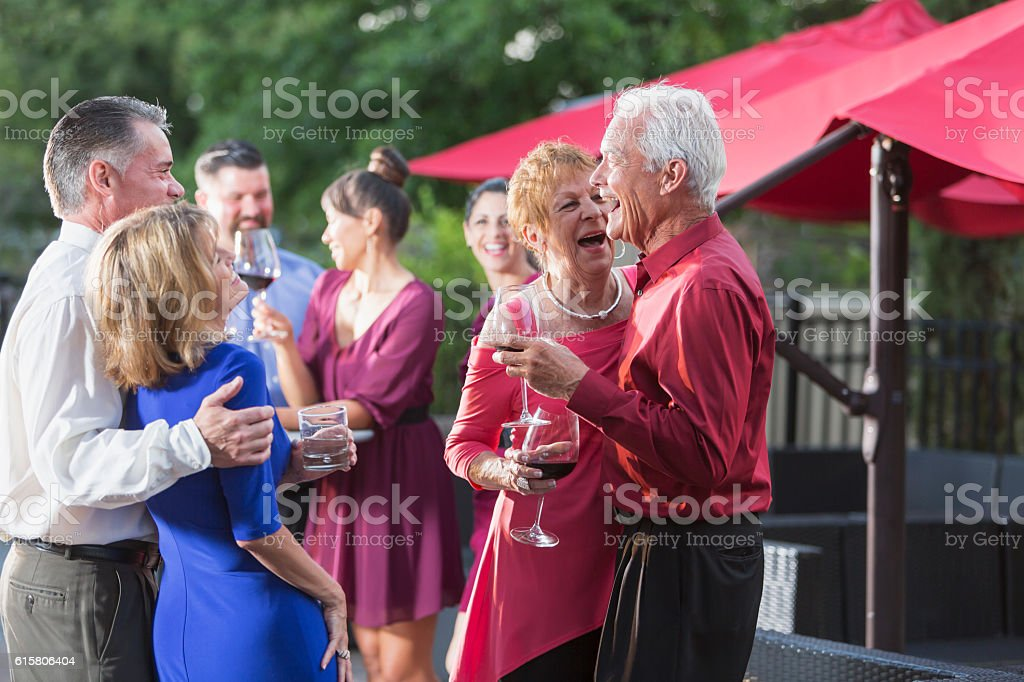 Group of people at a party laughing, drinking outdoors stock photo