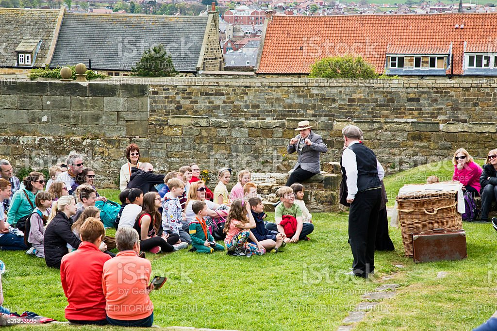 Group of people at Abbey ruins above whitby town 'editorial' royalty-free stock photo