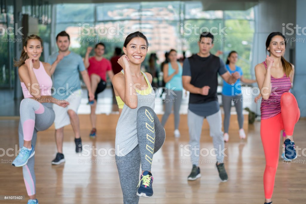 Happy group of Latin American people at the gym exercising in an...