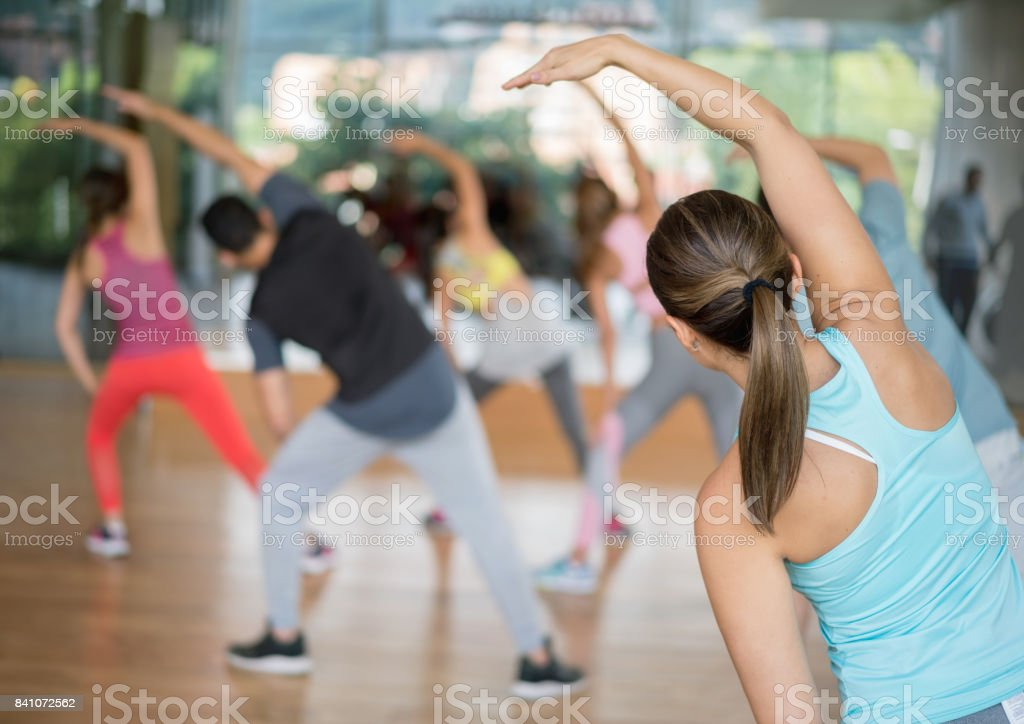 Rear view of a group of people exercising at the gym in an aerobics...