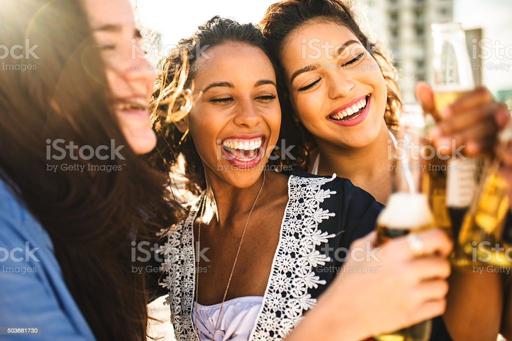 group of people cheering beers at dusk on the beach stock photo