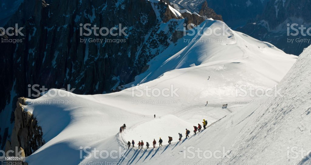 Group of People Climbing Snow Covered Mountain stock photo