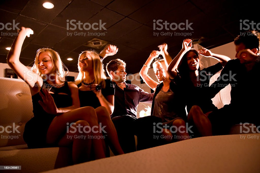 Group of people dancing on couch in nightclub royalty-free stock photo