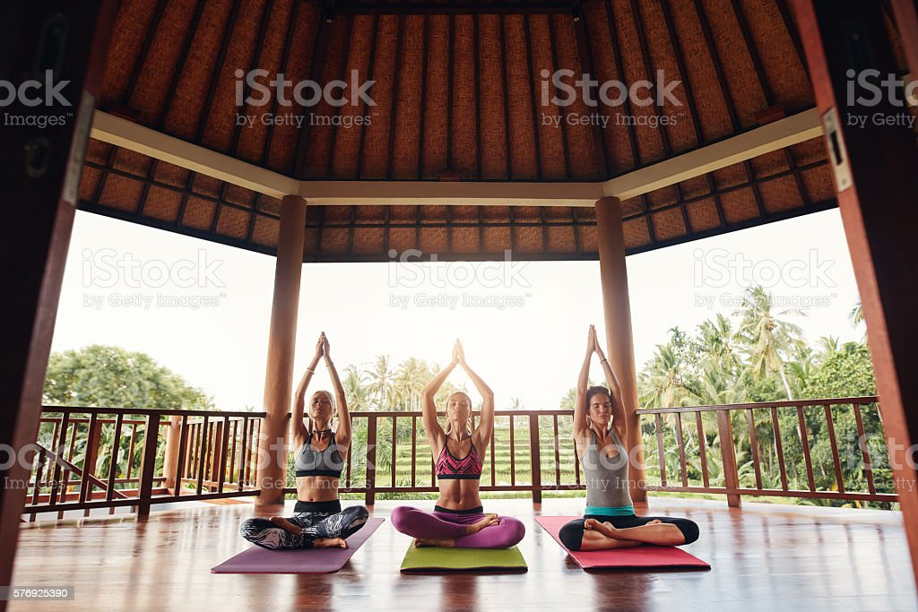 Group of people doing meditation in yoga class stock photo