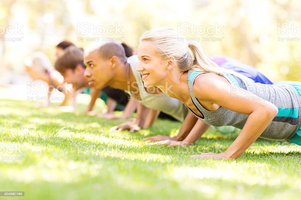 Group of People Doing Push-Ups At Bootcamp Workout Class stock photo