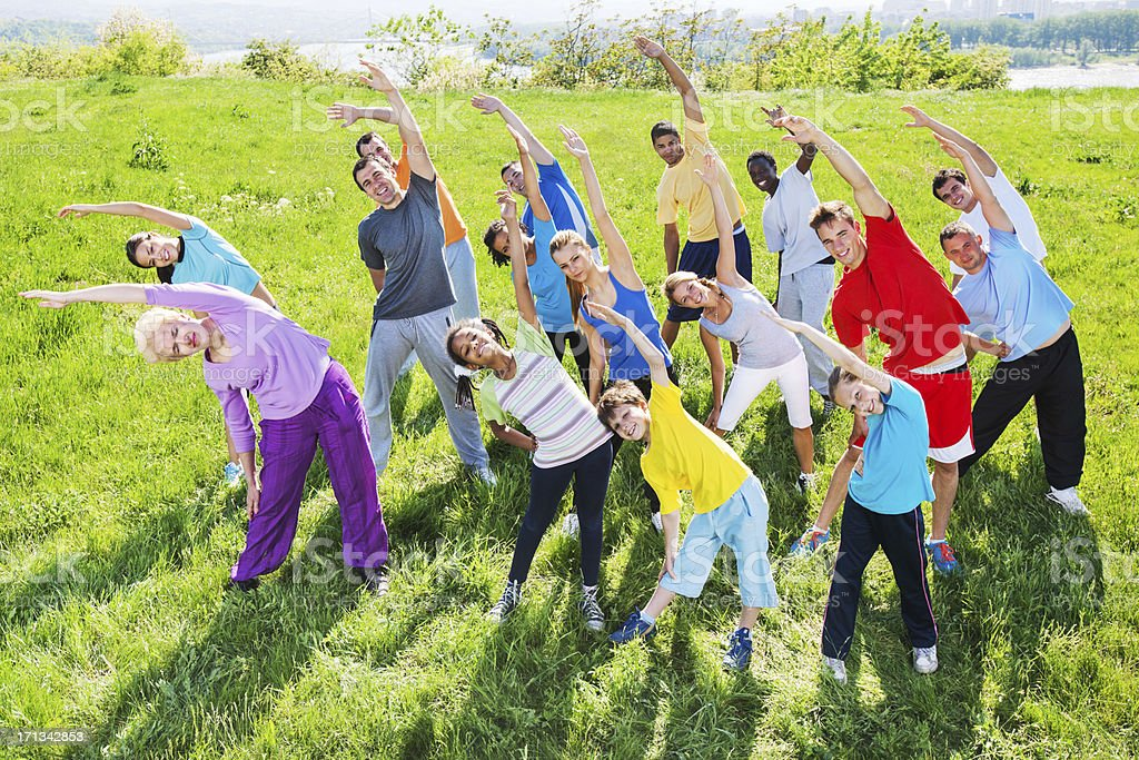 Group of people doing stretching exercises in field. royalty-free stock photo