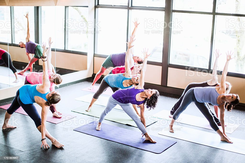 Group of people doing yoga class in a studio stock photo