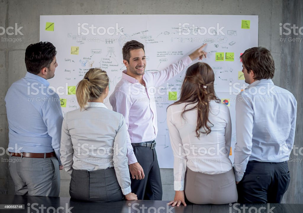 Group of people drawing a business plan stock photo