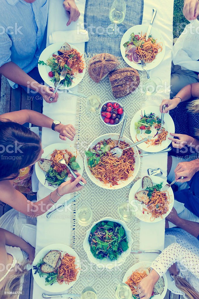Group of people eating around a long table. stock photo