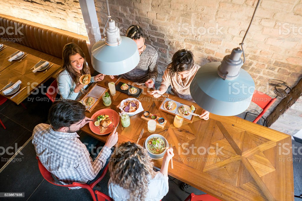 Happy group of people eating together at a restaurant and laughing