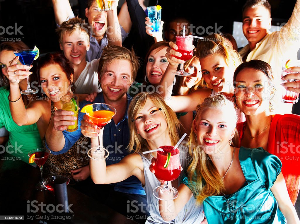 Group of people enjoying cocktails in a bar stock photo