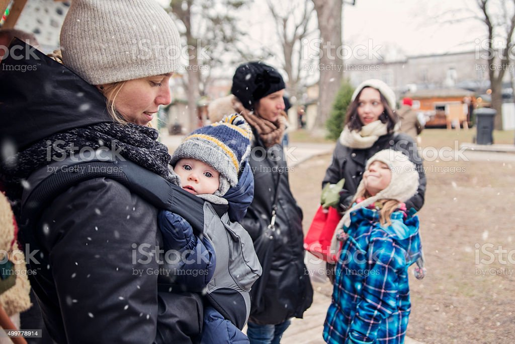 Group of people enjoying first snow in a public park. stock photo