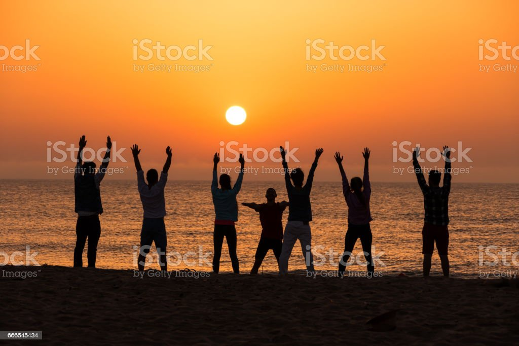 Group of people excercising on beach at dawn stock photo