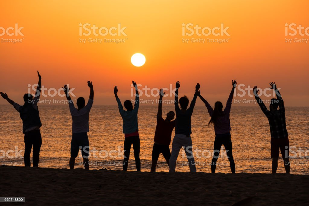 Group of people excercising on beach stock photo