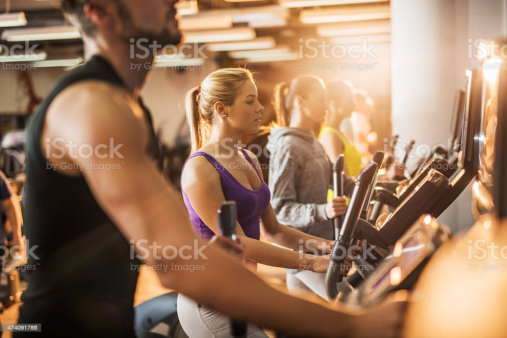 Group of people exercising on exercise machine in a gym. stock photo