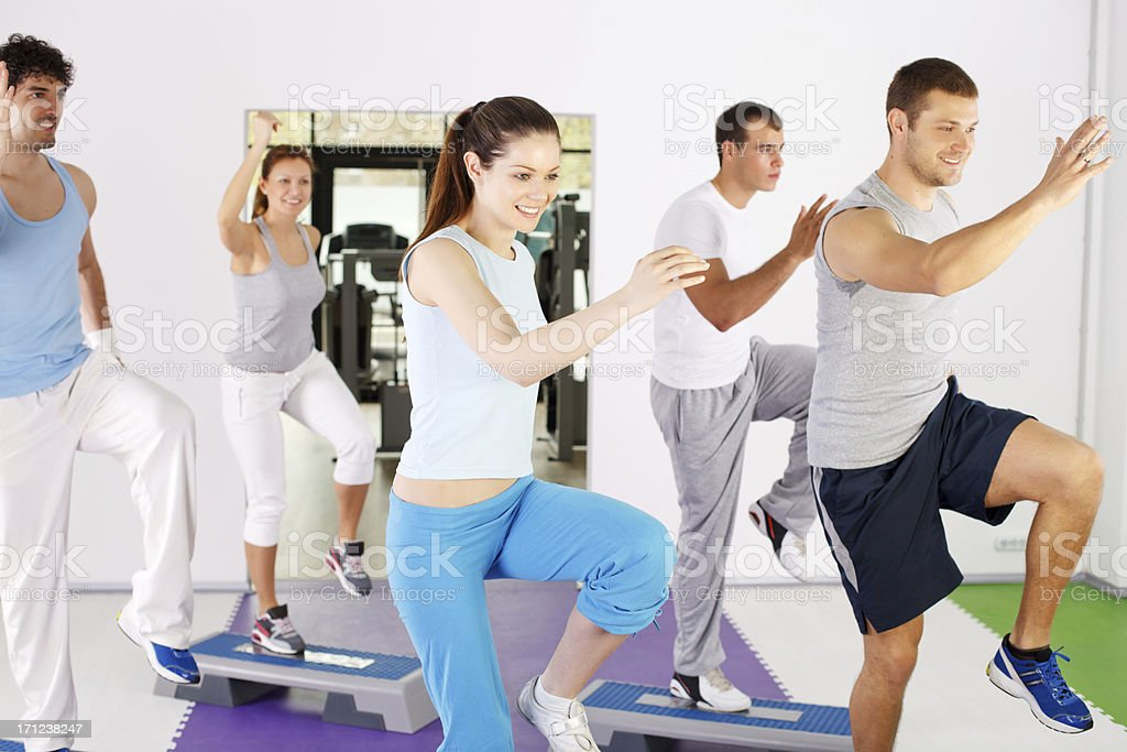 Group of people exercising on steppers. stock photo