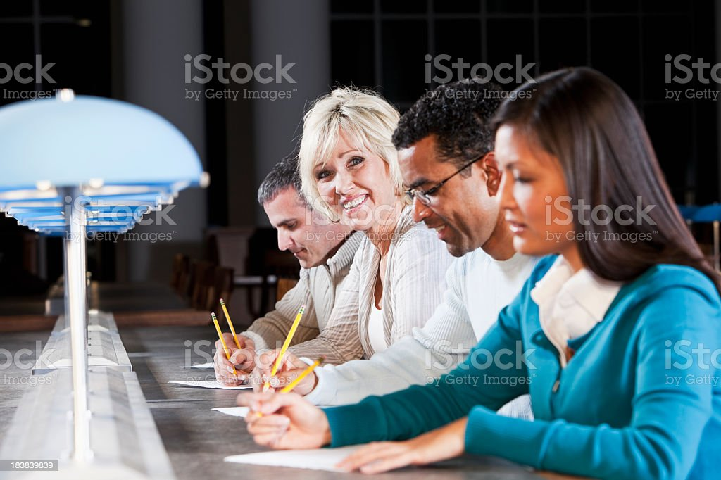 Group of people filling out paperwork stock photo