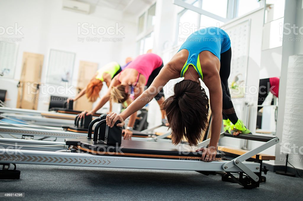 Group of people having a Pilates class on exercise machines. stock photo