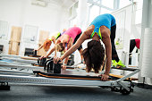 Group of people having a Pilates class on exercise machines.