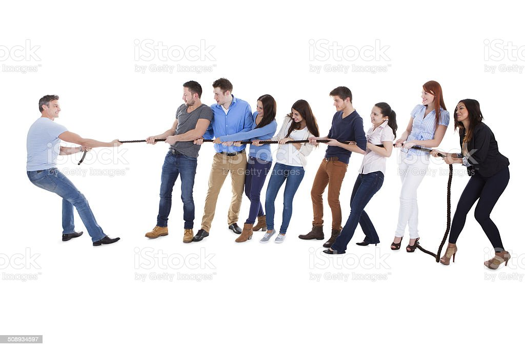 Group of people having a tug of war stock photo
