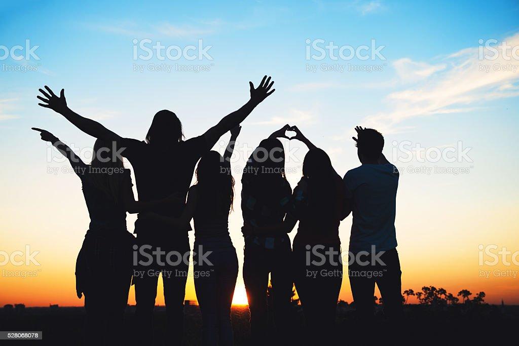 Group of people having fun outdoors; sunset stock photo