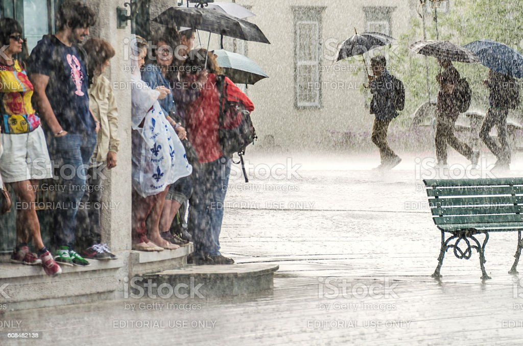 Group of people hide from heavy rain under a building. stock photo